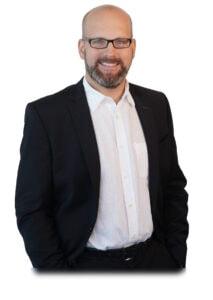 Foto des Firmengründer Michael Fritsch, dunkler Anzug, weißes Hemd, Brille